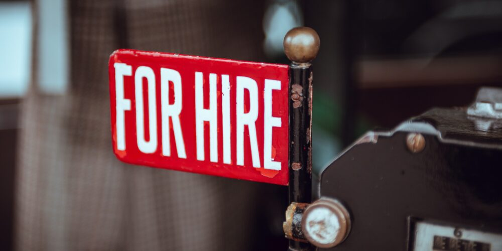 For hire sign in red with bold white capitalised writing