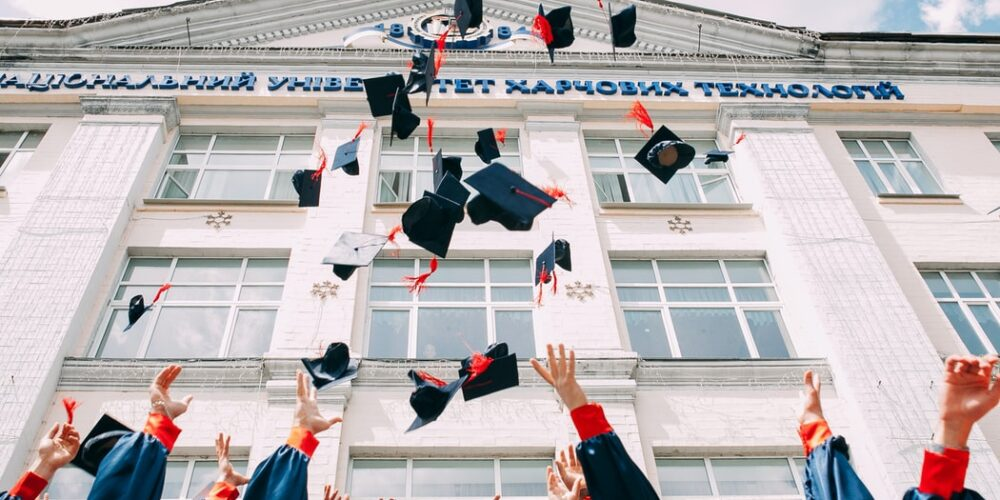 Graduated students throw their caps in the air outside a university